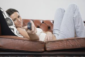 Young woman holding remote control, lying on sofa